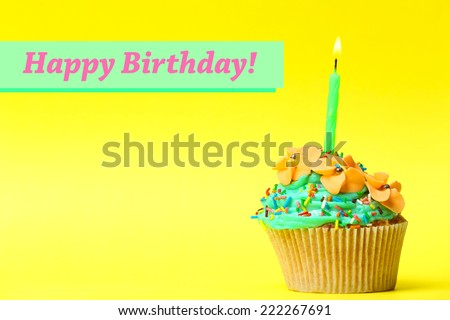 Delicious birthday cupcake on yellow background - stock photo