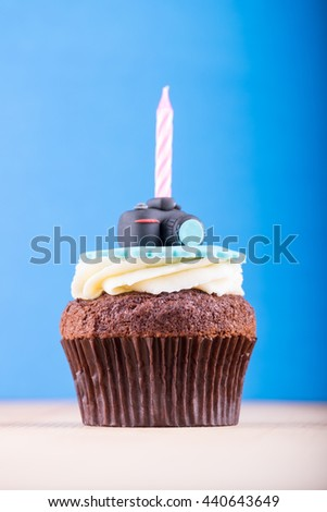 Delicious birthday cupcake with realistic camera icon on it and candle on wooden desk and blue background