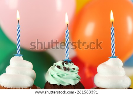 Delicious birthday cupcakes on bright background - stock photo