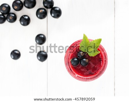 Delicious black currant smoothie in glass jar with fresh berries on white wood background. Top view or flat lay - stock photo