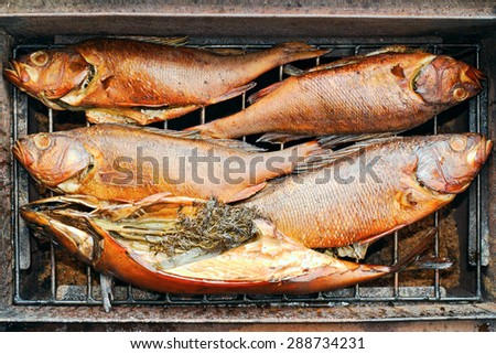 Delicious bloated fishes inside metal smoking box - stock photo