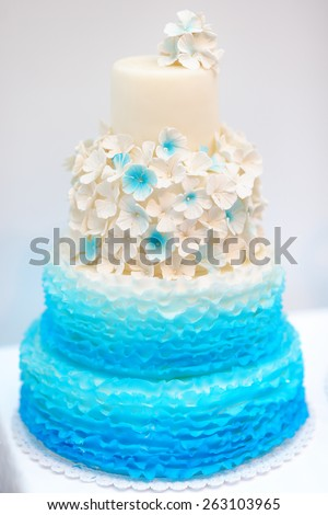 Delicious blue and white wedding cake decorated with cream flowers  - stock photo