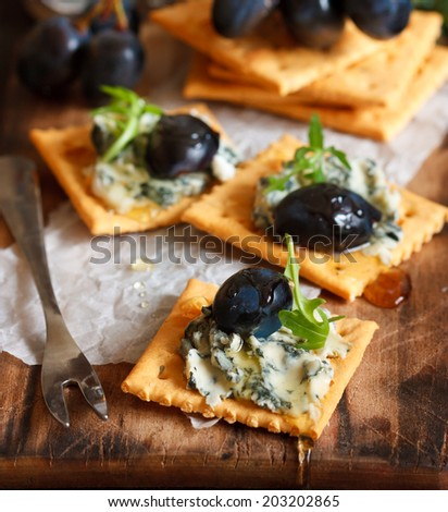 Delicious blue cheese crackers appetizer with honey, grape and arugula on an old cooking board. - stock photo