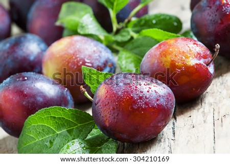 Delicious blue-orange plums with drops of water on the old wooden background, selective focus - stock photo