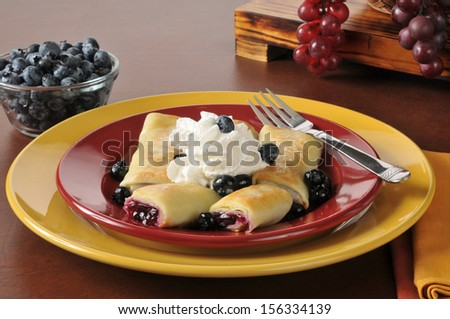 Delicious blueberry blintzes or crepes topped with whipped cream - stock photo