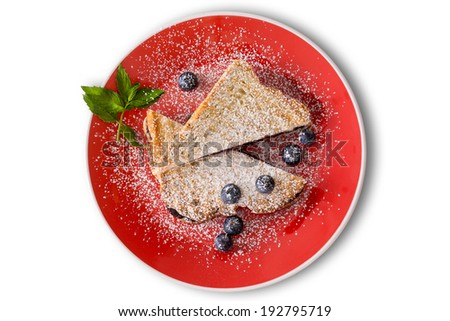 Delicious blueberry jam panini with fresh whole blueberries sprinkled with powdered sugar and garnished with mint served on a colorful orange plate, overhead view on white - stock photo