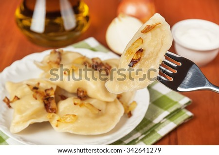 delicious boiled dumplings (varenyky) on ceramic plate with fried onion - stock photo
