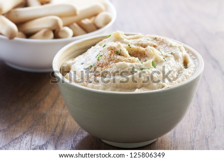 Delicious bowl of chickpea hummus with breadsticks - stock photo