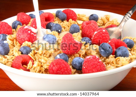 Delicious bowl of granola cereal with raspberries, blueberries and milk - stock photo
