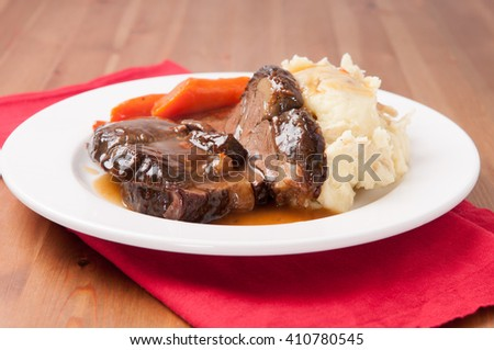 delicious braised beef roast with creamy mashed potatoes and roasted carrots and rice gravy - stock photo