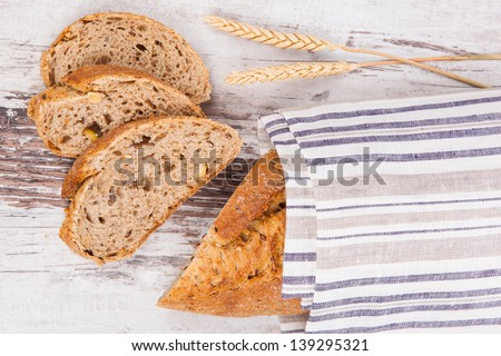Delicious bread background. Sliced whole grain bread on white wooden background with dry wheat, top view. - stock photo