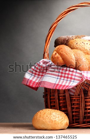 delicious bread in basket on wooden table on gray background
