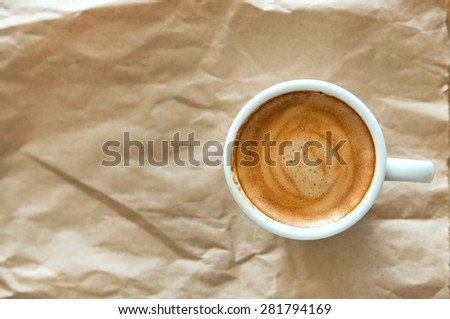 Delicious breakfast cup of strong aroma espresso coffee on a recyclable brown paper, copy space - stock photo