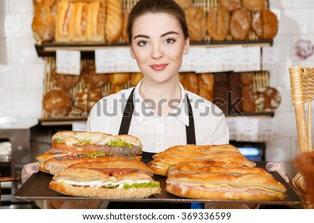 Delicious breakfast. Horizontal shot of a beautiful female bakery worker holding tray full of sandwiches - stock photo
