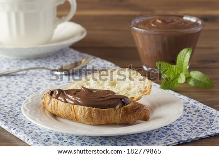 Delicious breakfast of croissant with chocolate cream on a blue napkin. A cup, a bowl, mint and a teaspoon. - stock photo