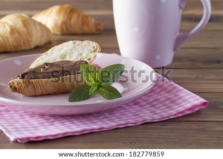 Delicious breakfast of croissants with chocolate cream on a pink checkered napkin. A pink cup and mint. - stock photo