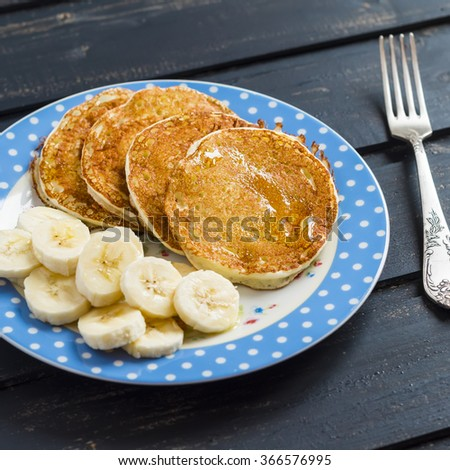 Delicious Breakfast pancake with honey and banana slices on dark wooden surface