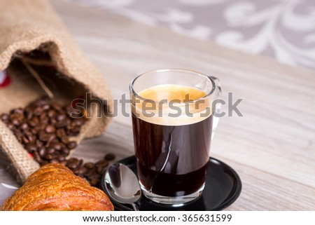 Delicious breakfast setting on gray wooden table with coffee in glass cup next to spoon and croissant on polka dotted napkin - stock photo