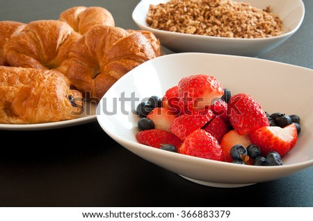 Delicious breakfast table with home made granola, croissants and strawberry and blueberry fruit salad. - stock photo