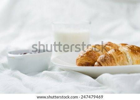delicious breakfast with croissants in bed - stock photo