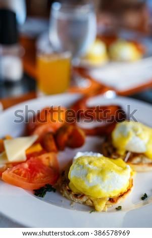 Delicious breakfast with eggs Benedict, bacon, orange juice and coffee - stock photo