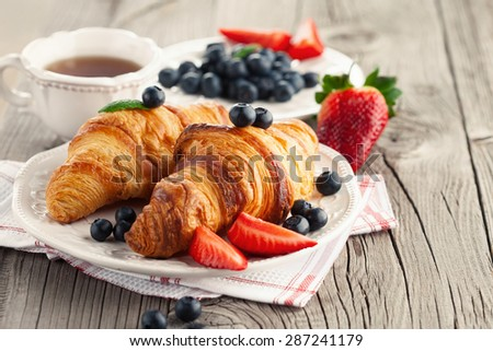 Delicious breakfast with fresh croissants and ripe berries on old wooden background, selective focus - stock photo