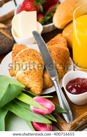 delicious breakfast with fresh croissants on wooden table