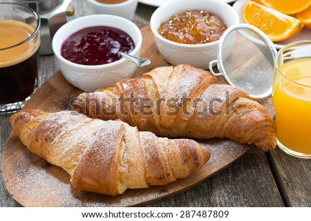 delicious breakfast with fresh croissants on wooden table, close-up, horizontal - stock photo