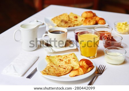 Delicious breakfast with fresh fruits, orange juice, pastry, pancakes and coffee served for two  - stock photo