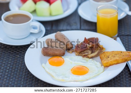 Delicious breakfast with fried eggs, bacon and sausages - stock photo