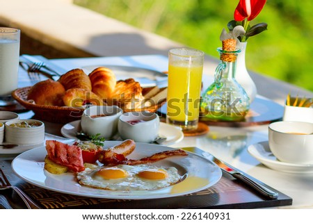 Delicious breakfast with fried eggs, vegetables, orange juice and coffee - stock photo