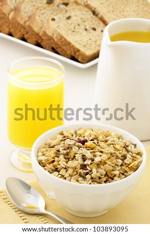 delicious breakfast with orange juice, whole grain bread and a healthy bowl of muesli cereal. - stock photo