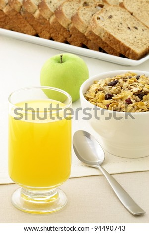 delicious breakfast with orange juice, whole grain bread,fresh apple and a healthy bowl of cereal. - stock photo