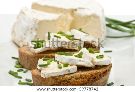 Delicious brie cheese on fresh sliced bread with chives - stock photo