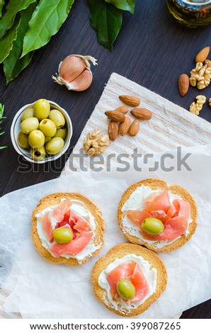 Delicious bruschetta with prosciutto and olives on background of garlic, Bay leaf and nuts. Italian appetizer. Top view. Vertical. - stock photo