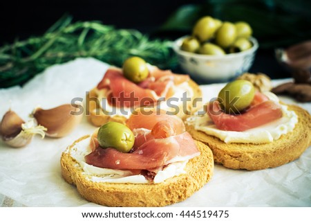 Delicious bruschetta with prosciutto and olives on background of rosemary, garlic and Bay leaf. Italian appetizer. Selective focus. - stock photo