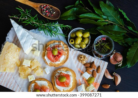 Delicious bruschetta with prosciutto and olives with cheese Parmesan and Bree on background of olive oil with spices, rosemary, garlic, Bay leaf, nuts and wooden spoon with pepper. Top view.  - stock photo