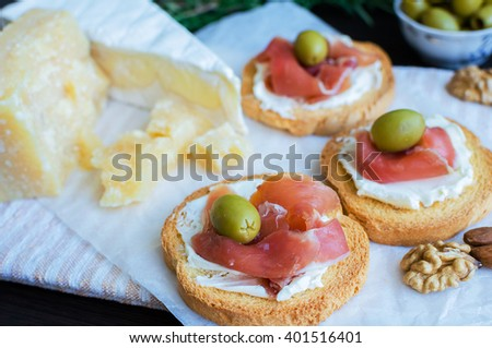Delicious bruschetta with prosciutto and olives with cheese Parmesan and Bree, rosemary and nuts. Italian appetizer. Selective focus. - stock photo