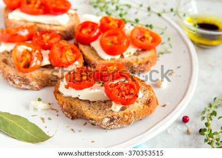 Delicious bruschetta with roasted tomatoes, feta cheese and herbs on white plate - stock photo