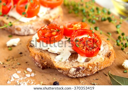 Delicious bruschetta with roasted tomatoes, feta cheese and herbs on wooden board - stock photo
