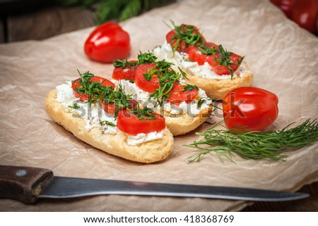 Delicious bruschetta with tomatoes, feta cheese, dill and spice on wooden board - stock photo