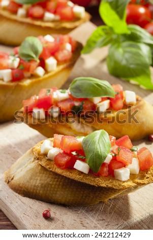 Delicious bruschetta with tomatoes, mozzarella and herbs - stock photo