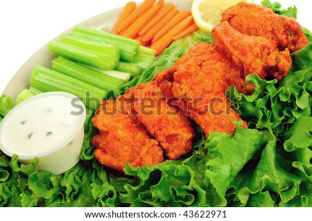 Delicious buffalo chicken wings served with celery, carrots and chunky blue cheese dip - stock photo