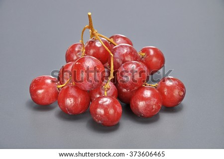 Delicious bunch red seedless crimson grape on grey background.