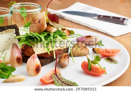 Delicious burger served on white plate with onions, tomatoes, arugula and rye bread. Knife in background for cutting the meal. - stock photo