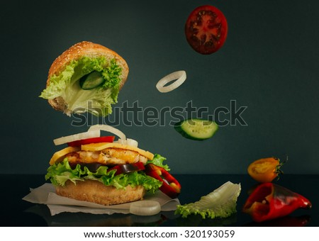 Delicious burger with flying tomato, cucumber and onion slice on dark background - stock photo