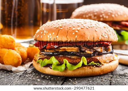 Delicious burger with fried potato balls and beer - stock photo