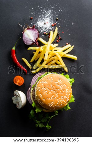 Delicious burgers and fries on a black background. View from above