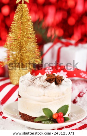 Delicious cake on saucer with holly and berry on bright Christmas decoration background - stock photo