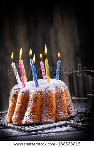 delicious cake with burning candles for birthday party on rustic background - stock photo